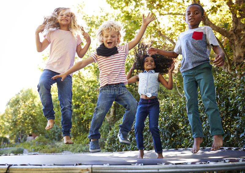 Four kids having fun together on a trampoline in the garden stock photo