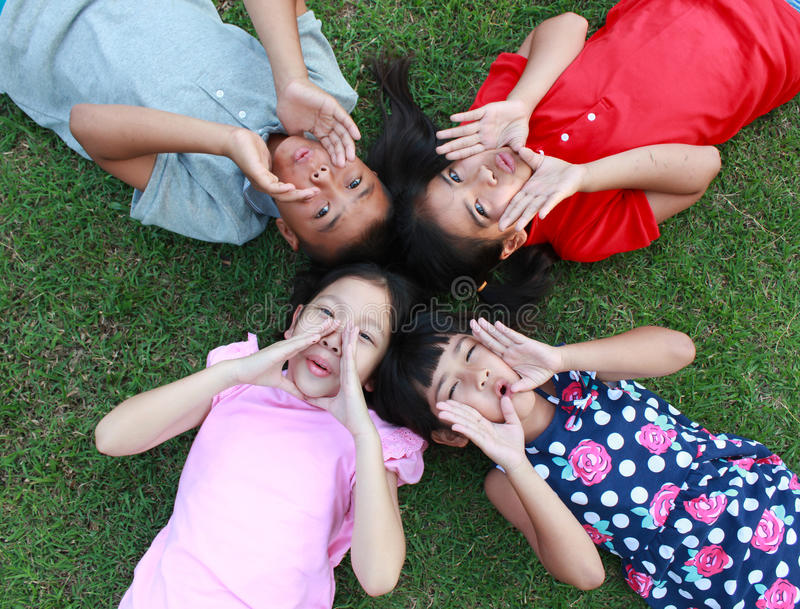 Four kids having good time in the park. Four kids having good time in the park, yelling on green grass background royalty free stock images