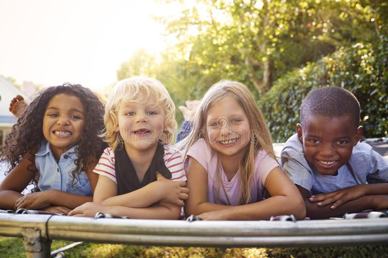 Four kids lying down together on a trampoline in the garden stock photography