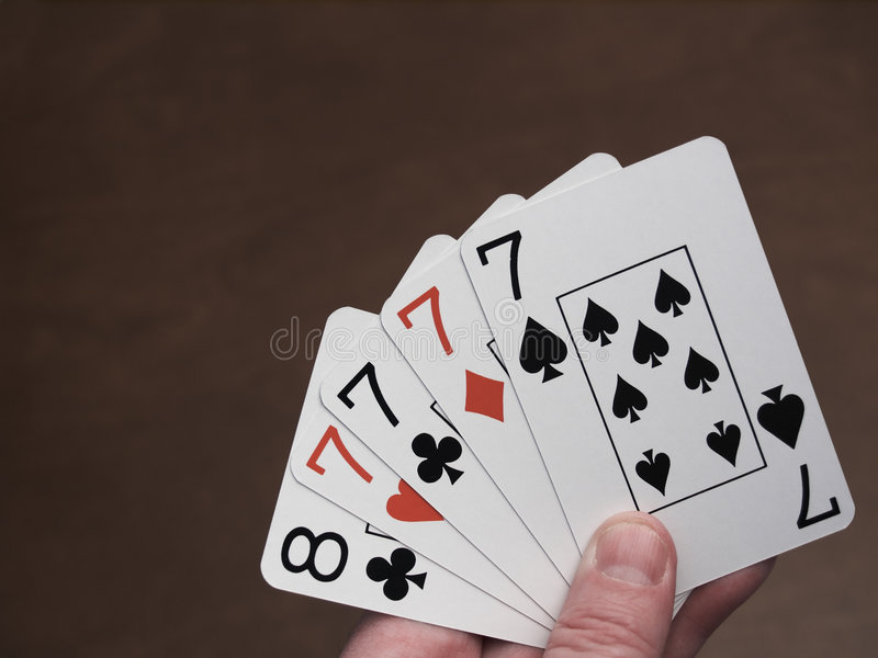 Four of a kind. Poker hand, four of a kind, sevens royalty free stock image