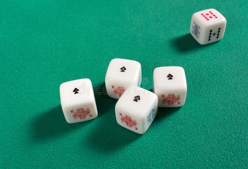 Four of a Kind on Poker Dice. Poker dice on a green table with a four of a kind of aces stock photo