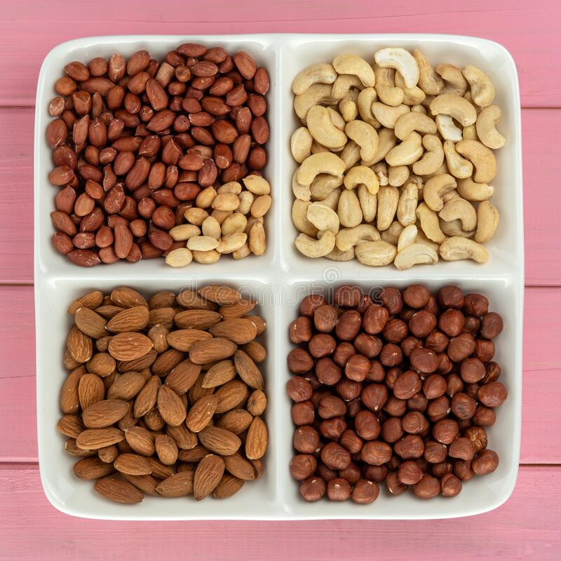 Four kinds of nuts in four compartments on a pink background: stock photos