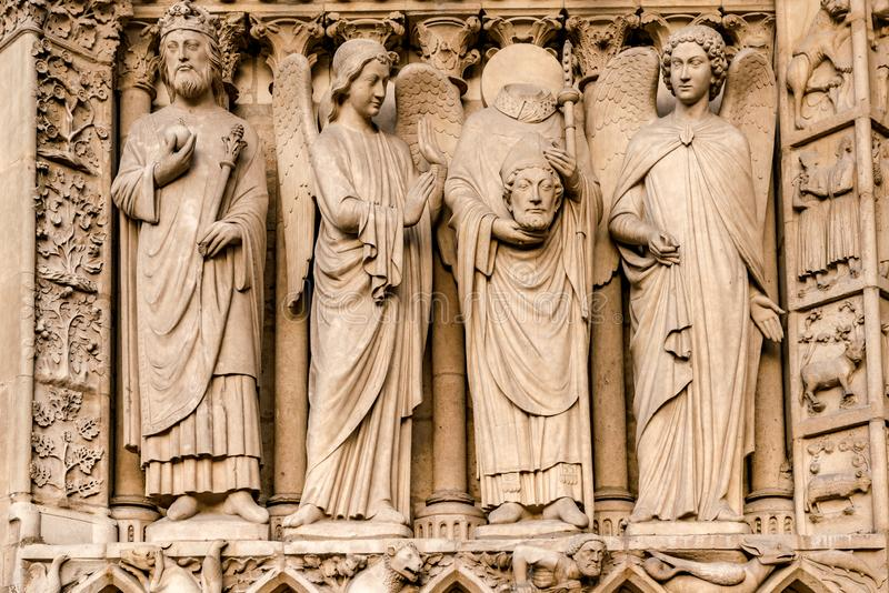 The four large statues of the left-hand side of the portal of the Virgin represent an unidentified king and Saint Denis royalty free stock images