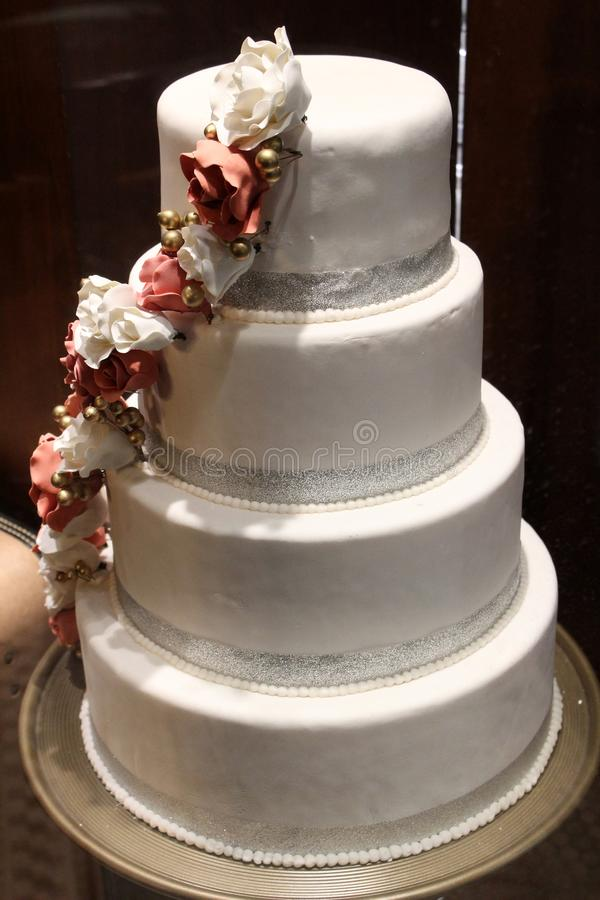 Four layer cake decorated with white frosting and sweep of candy flowers royalty free stock photography