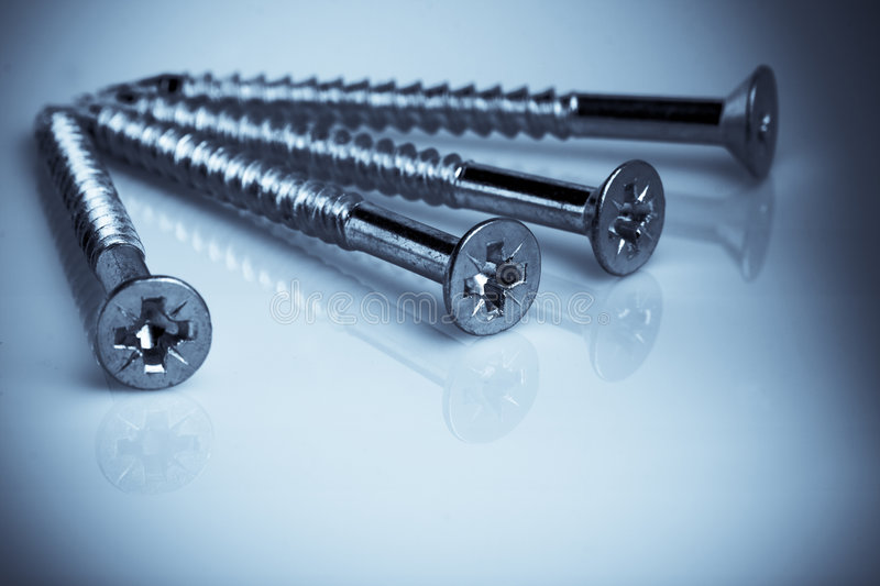 Four laying screws. Four laying blue tint screws o the smooth plastic surface royalty free stock photo