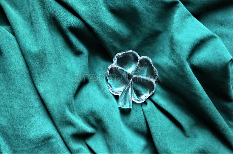 Four leaf clover symbol of a St Patrick day. On green background, copy space royalty free stock photos
