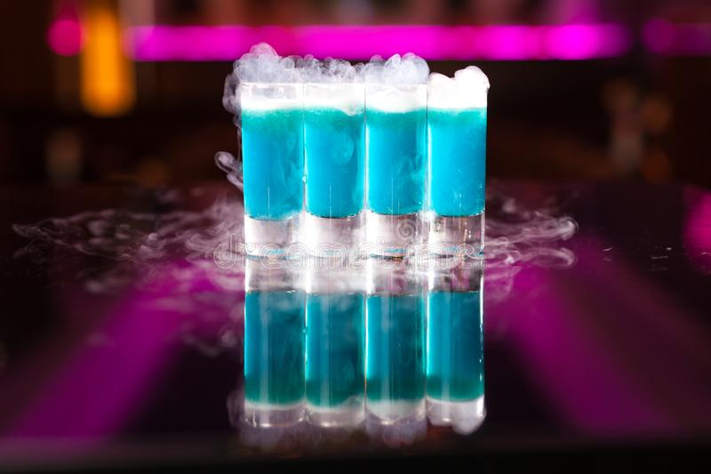 Four light blue cocktail shots with smoke on reflective mirror table stock image