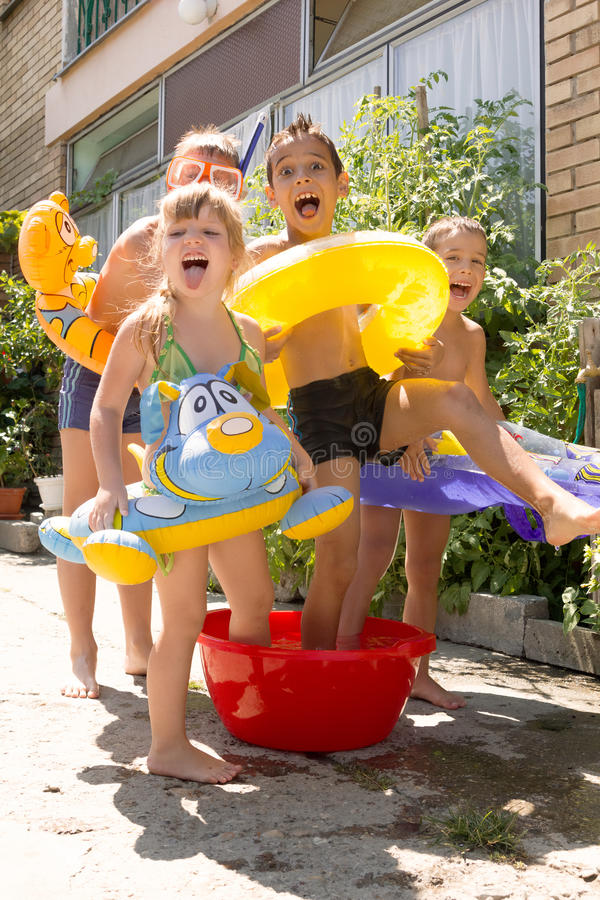 Four little children splashing and having fun. In their yard,summer play royalty free stock images