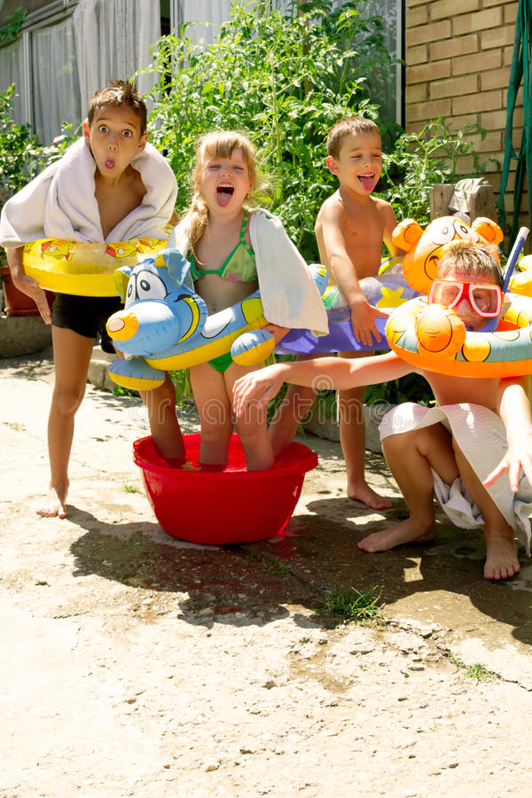 Four little children splashing and having fun. In their yard,summer play stock images