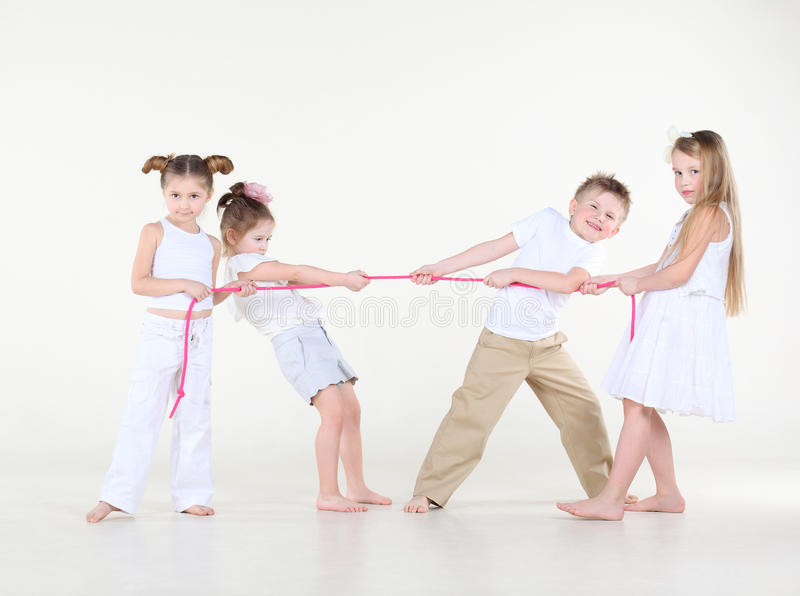 Four little children in white pull pink rope. stock images