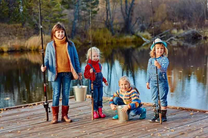 Four little girls catch fish on a wooden pontoon.Weekend at the lake. Fishing with friends. royalty free stock images