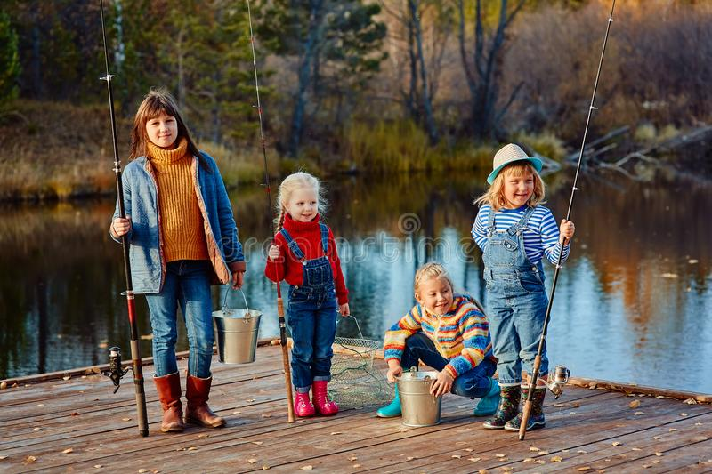 Four little girls catch fish on a wooden pontoon.Weekend at the lake. Fishing with friends. royalty free stock photos