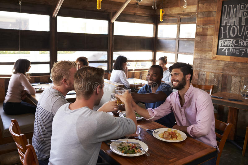 Four male friends making a toast at a table in a restaurant royalty free stock images