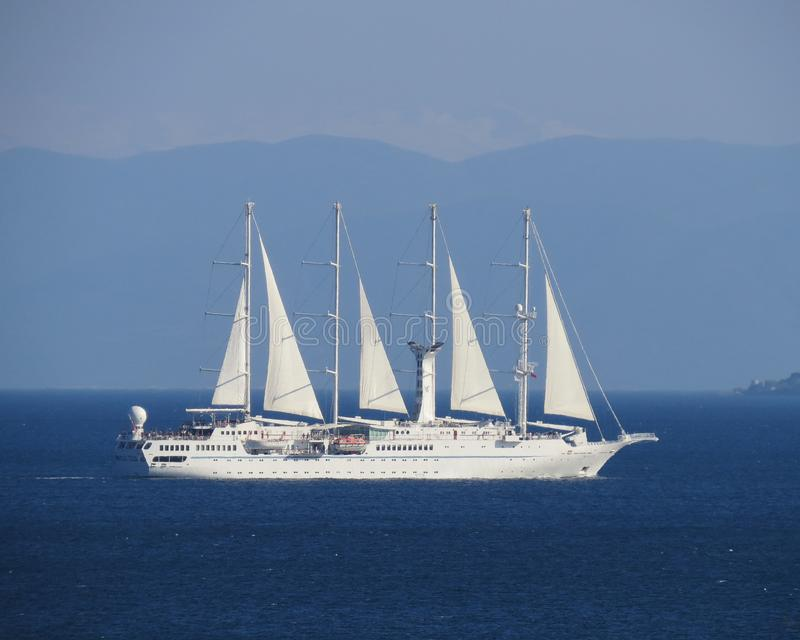 A four-mast white ship under sail moves across the blue sea. Close-up royalty free stock photo
