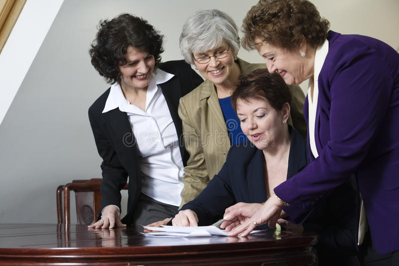 Four mature business women. View of business women discussing documents stock photo