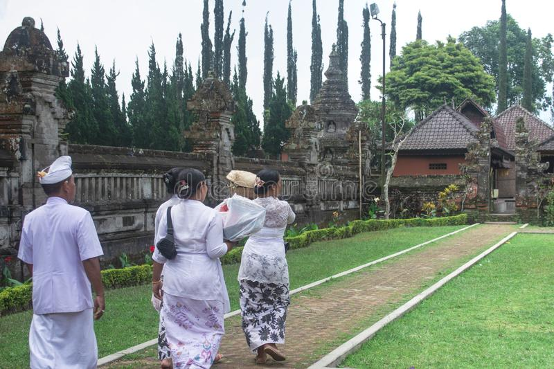 Four Member of Balinese Family Wearing White Clothing Going To Hindu Temple for Praying Bringing Sesajen on The Basket stock photography