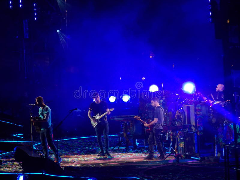 Four Members of Band Coldplay on Stage in Concert. The four members of the band Coldplay (Chris Martin, Jonny Buckland, Guy Berryman, and Will Champion) play royalty free stock photos