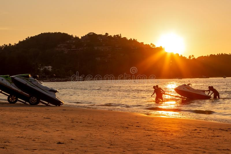 Four mens at sunset pull hydrocycle out of the water. Workers of the beach. Water bike loaded onto a rickshaw trailer.  stock photos