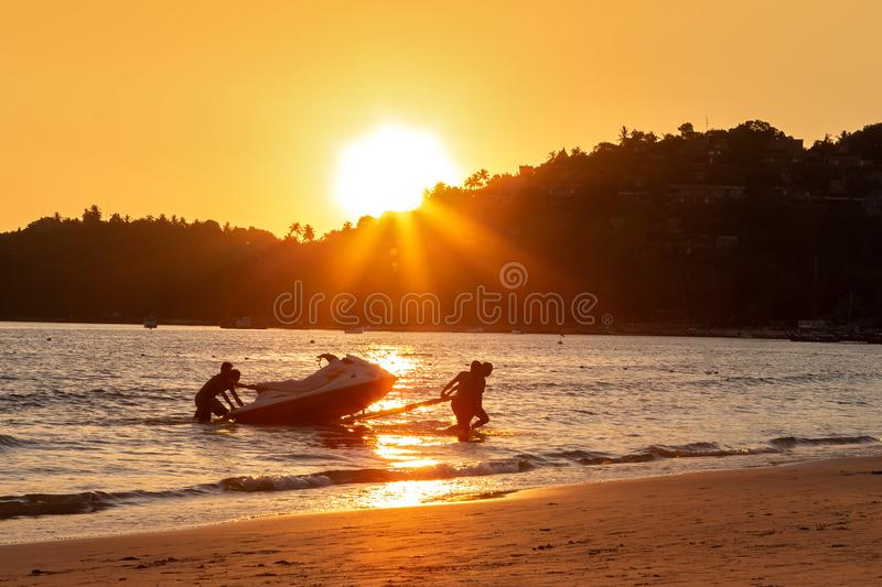 Four mens at sunset pull hydrocycle out of the water. Workers of the beach. Water bike loaded onto a rickshaw trailer.  stock photography