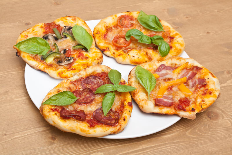 Different Kinds Of Small Pizza On A White Plate On Wooden Table
