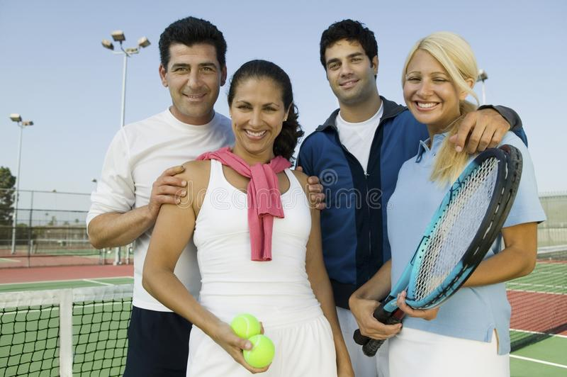 Four mixed doubles tennis players. By net at tennis court, portrait stock image
