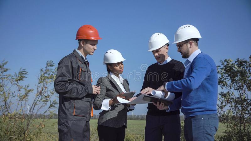 Four engineers standing in open field. Four mixed ethnic people in multicolored jackets and hard hats standing in open field next to large white windmill stock images