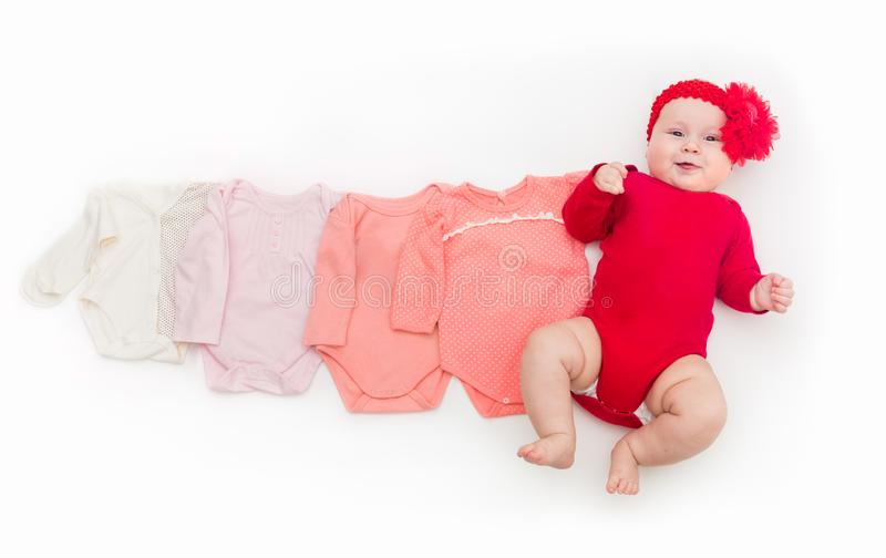 A four month happy baby in red bodysuit lying on a white background with pink clothes smaller size. The concept of a growing organism stock images