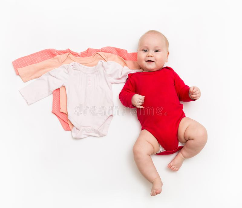 A four month happy baby in red bodysuit lying on a white background with pink clothes smaller size. The concept of a growing organism stock photography