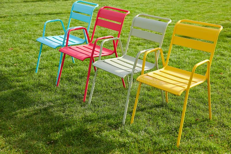 Four multi-colored chairs stand on a green lawn on a summer evening. Image of a comfortable place to relax in an urban environment. Four multi-colored chairs royalty free stock images