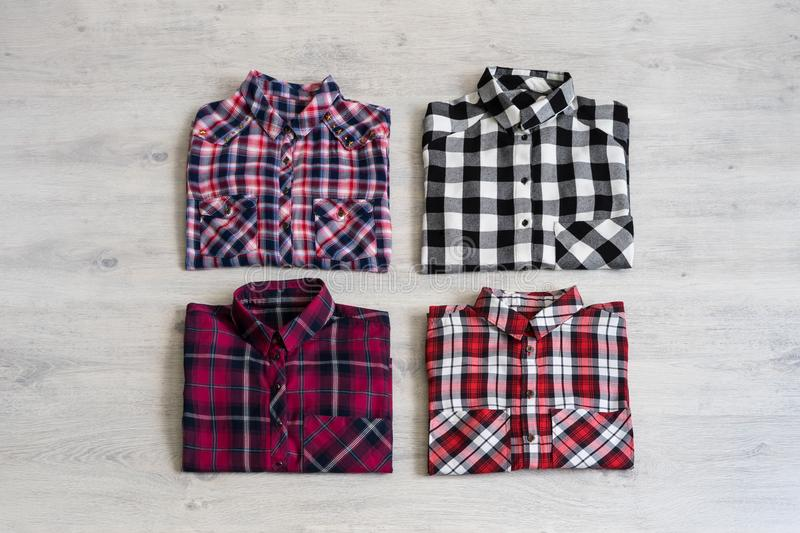 Four multi-colored checkered women`s shirts lying neatly folded stock photo
