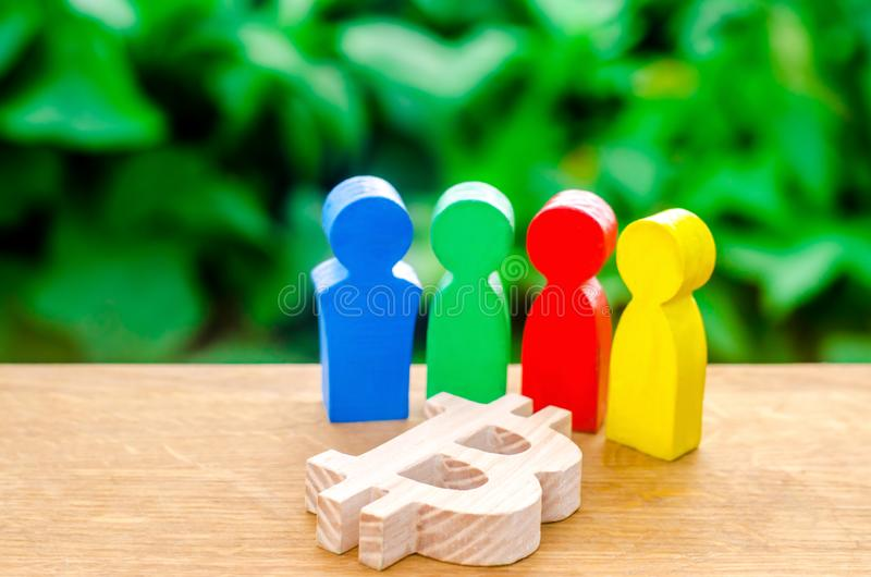 Four multi-colored figures of people surround a bitcoin figure. Conceptual conduct of activities around cryptocurrency stock image