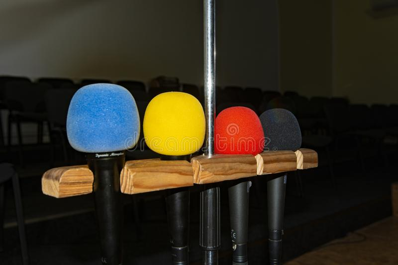 Four multi-colored microphones on a stand in an empty room with chairs without people royalty free stock photo