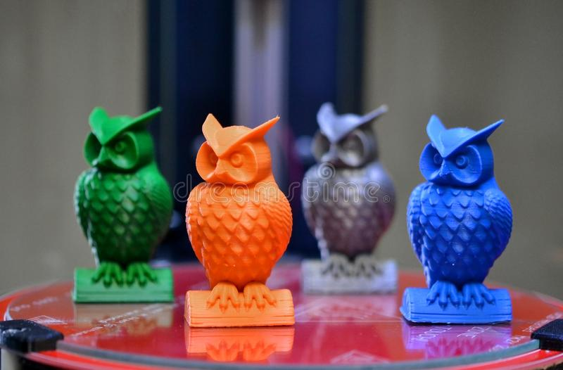 Four multicolored models of owls created on a 3d printer stand close-up. Four multicolored models of owls created on a 3d printer stand on the desktop of 3d stock images