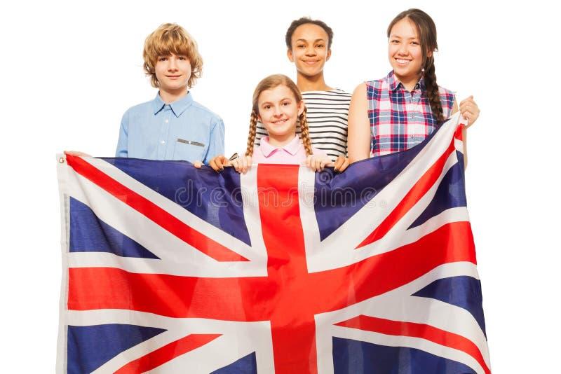 Four multiethnic teenage kids with British flag. Four multiethnic teenage kids standing behind British flag, isolated on white background stock image