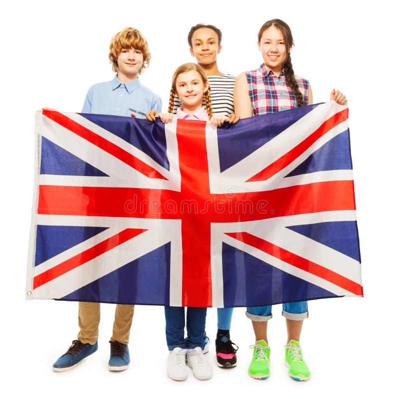 Four multiethnic teenage kids holding British flag. Four multiethnic teenage kids standing behind and holding British flag, on white background royalty free stock images