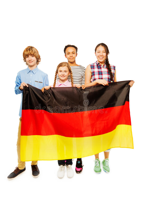 Four multiethnic teenage kids holding German flag. Group of four happy multiethnic teenage kids standing behind the flag of Germany, on white stock photo
