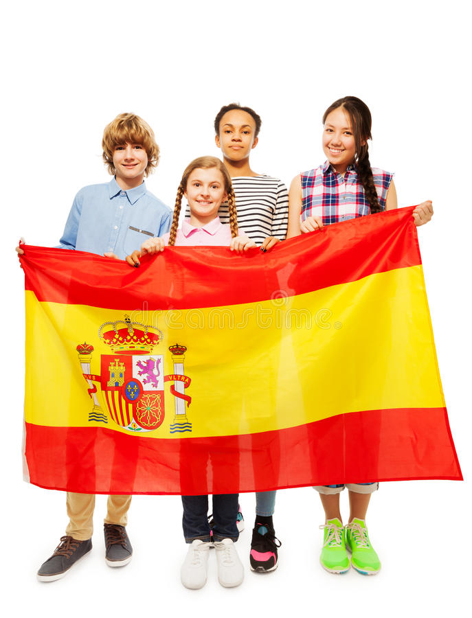 Four multiethnic teenage kids holding Spanish flag. Group of four happy multiethnic teenage kids standing behind the flag of Spain, isolated on white royalty free stock image
