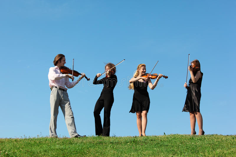 Four musicians play violins against sky