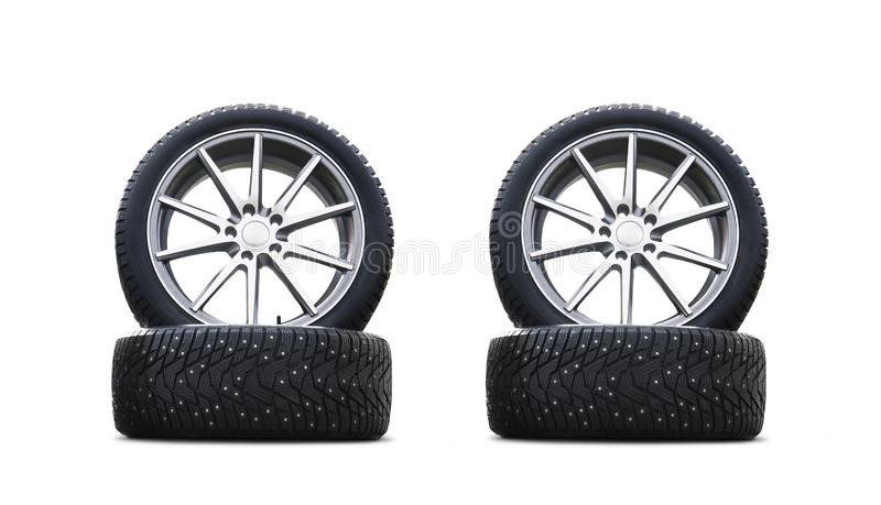 Four new good-looking snow tires isolated on the white background. A set of studded winter car tires. A set of wheels and tyre pac royalty free stock photo
