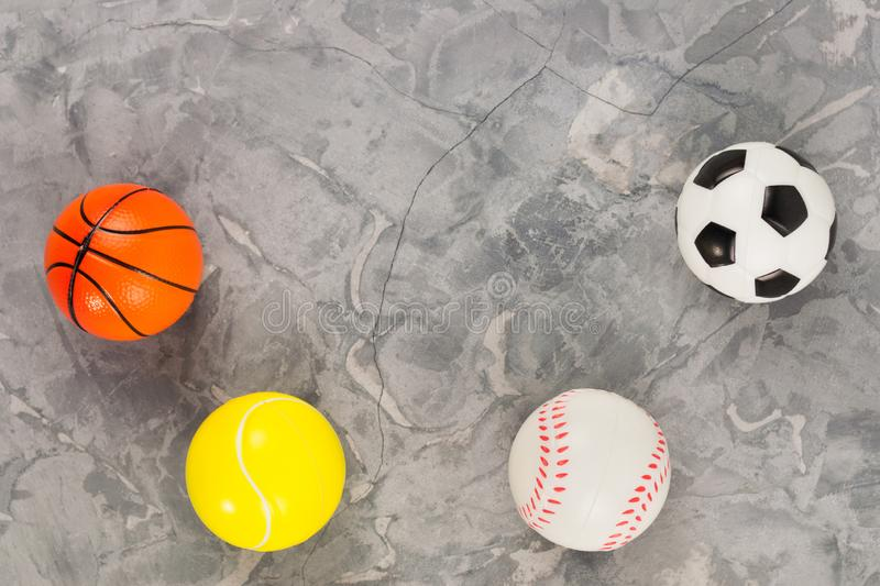 Four new soft rubber basketball and baseball and tennis and soccer balls on old worn cement royalty free stock image