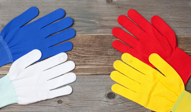 Four new working multicolored gloves. On a old wood boards stock photo
