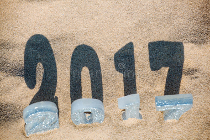 Four New Year`s figures are in the sand on the beach or seaside, cast a large shadow on the ground. stock images