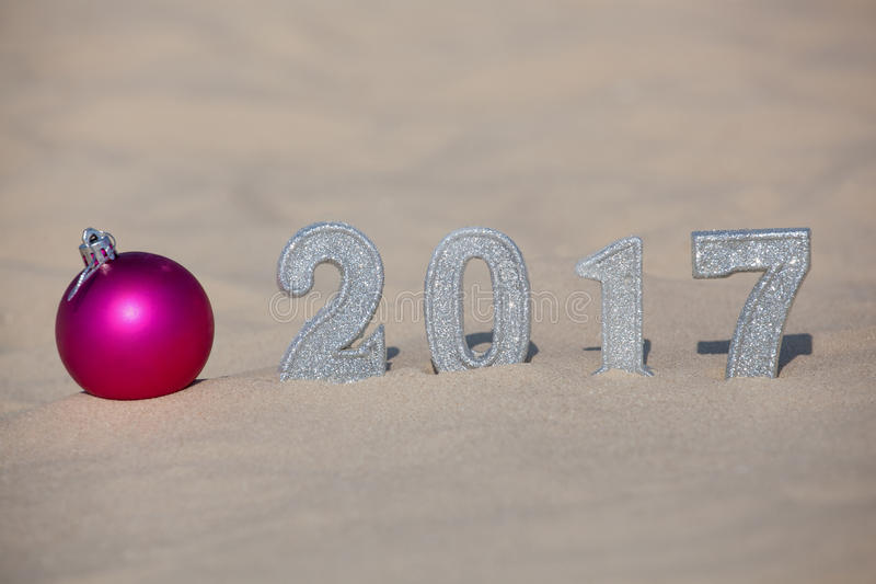 Four New Year`s figures are in the sand on the beach or seaside, cast a large shadow on the ground. Near the sand is pink ball. royalty free stock image