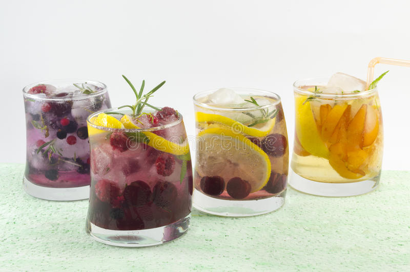 Four non alcoholic fruit cocktails arranged on the green table w stock images