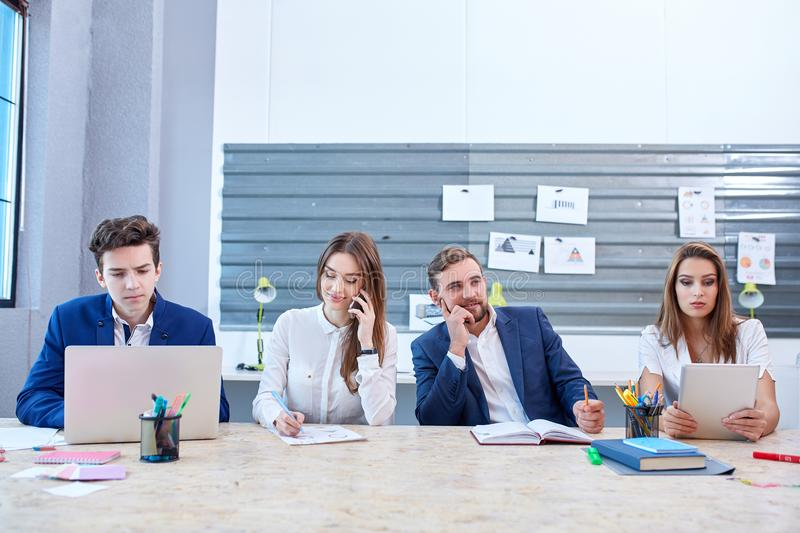 Four office workers are sitting in the office and working, one of them looks up thoughtfully. Four office workers of guys and girls in business suits sit at the stock photo