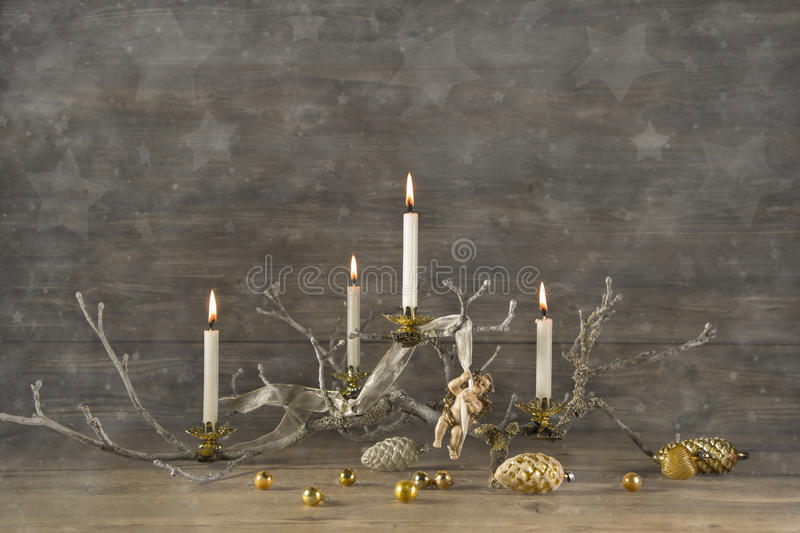 Four old burning advent candles on wooden rustic christmas background. Four old burning advent candles on wooden rustic christmas background with stars stock photography