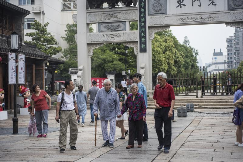 Four old people walked past the old gate of the East Gate. stock photo