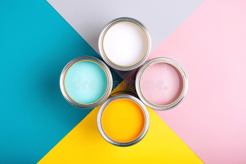 Four open cans of paint on bright symmetry background. royalty free stock image