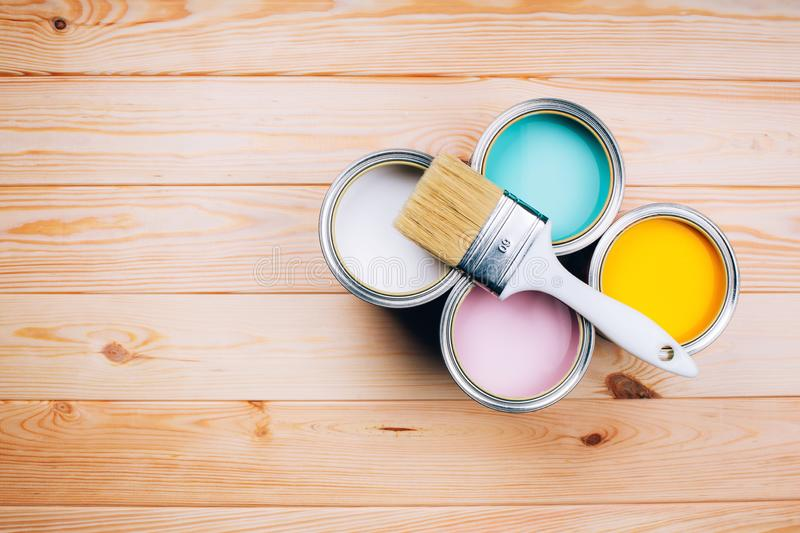 Four open cans of paint with brush on them on wooden natural background. royalty free stock photography
