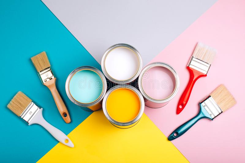 Four open cans of paint with brushes on bright background. stock photos